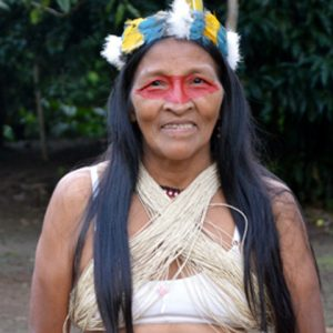 Indigenous woman smiles with long hair, red face paint and feathers crown