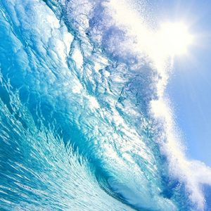 Look from below at closing ocean wave with sun in the background