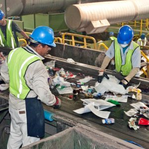 Workers at a recycling facility sorting waste