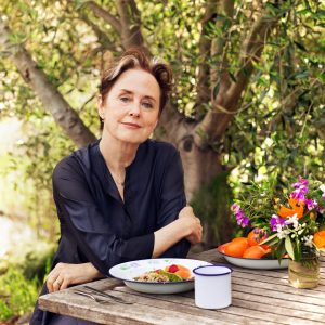 Alice Waters sitting at table outdoors with fresh food and flowers
