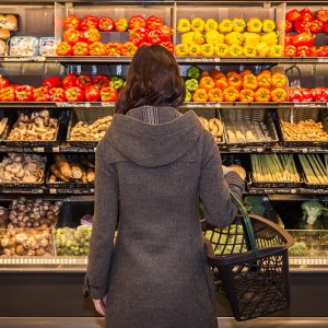 Woman standing in grocery store looking at produce
