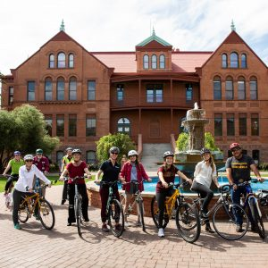Several ASU students and staff on bikes outside of Old Main at ASU