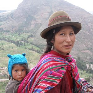 Quechua woman carrying toddler on her back with traditional attire and mountains on the background