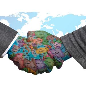 Two executives hands shaking with world map projected on their skin
