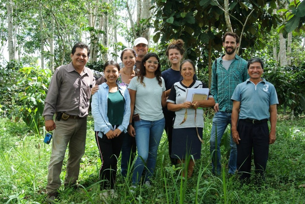 Group of people standing together in lush coffee plantation