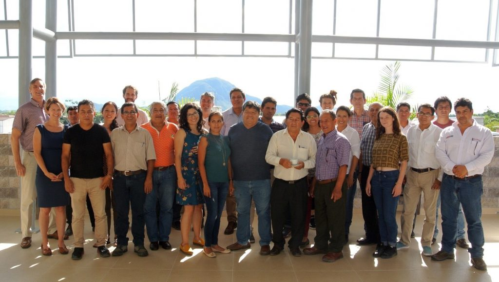 Nearly 30 workshop participants standing indoors together with mountain in background