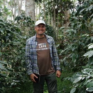Man standing and smiling in lush coffee plantation