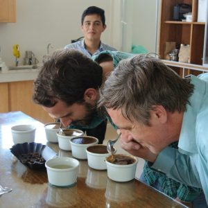 Two men bending down testing coffee samples on table