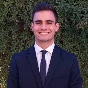 Dawson Morford - ASU sustainability student - wearing navy blue suit smiles in front of plant wall
