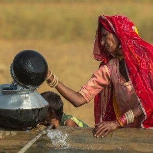 Indian woman pouring water into a large bowl