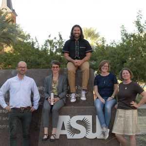 ASU Professors sitting and standing near ASU sign