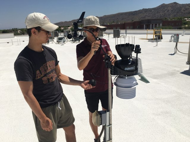 Dr. Vanos and a colleague installing a roof-top monitoring instrument.