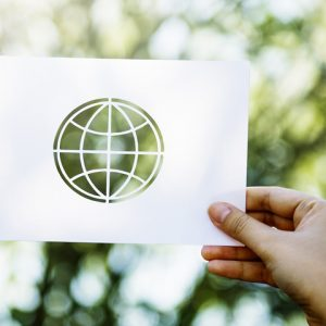 Hand holds piece of white paper template of the world against trees background