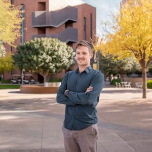 Man stands on ASU campus with crossed hands and smile