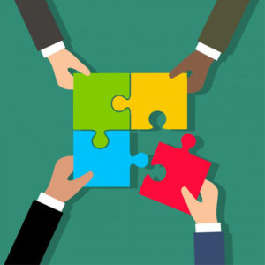 Computer illustration of four hands holding four puzzle pieces that fit together