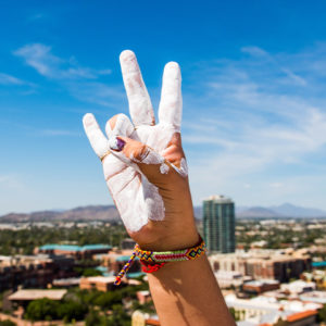 Hand of student painted in white making ASU forks hand gesture