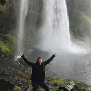 Woman with arms raised smiling in front of waterfall