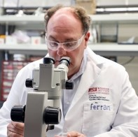 Man wearing lab coat looks into microscope