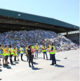 workers in green vests at recycling center