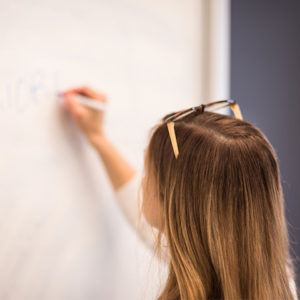 """Woman writing the word """"priorities"""" on a dry-erase board"""